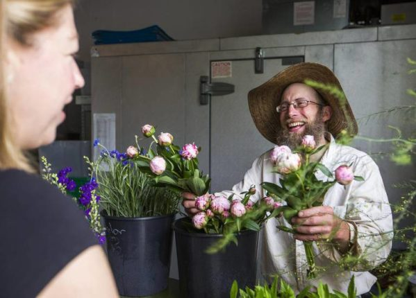 Matt Clayton, owner of Wild Scallion Farm, sells flowers during the grand opening of Piedmont Wholesale Flowers on Thursday.
